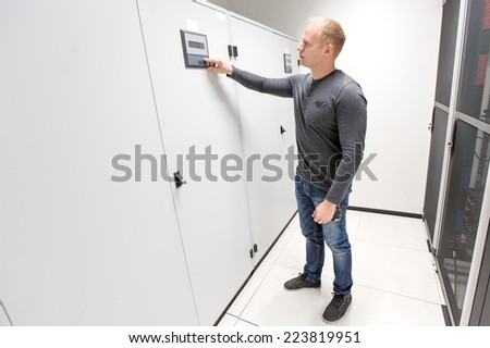 IT engineer adjusts air conditioner in datacenter - stock photo