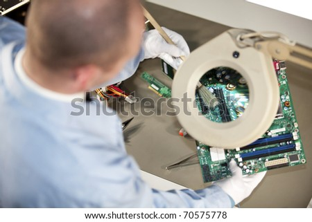 IT engineer cleaning a motherboard - stock photo
