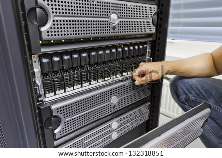 It engineer / consultant working in a data center. Holding a disk cabinet front and look at the disks. This enclosure in a SAN (storage area network).