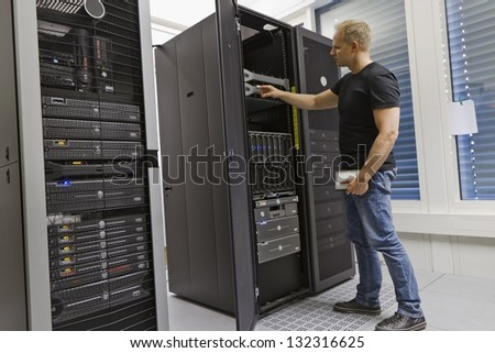 It engineer / consultant working in a data center. Holding a hard drive and opning a server. - stock photo