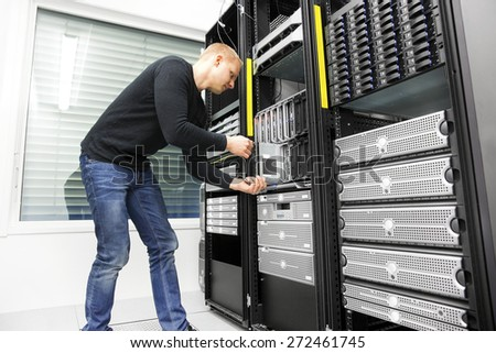 IT engineer installs blade server in datacenter - stock photo