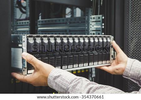 IT Engineer installs equipment in the rack in datacenter - stock photo