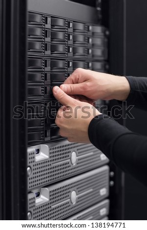 It engineer / technician working in a data center. This enclosures is a SAN (storage area network) and servers bellow.