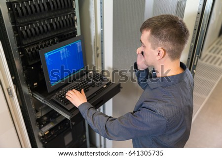 IT engineer with the management console between the server racks in the data center