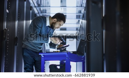 IT Engineer with Tool Cart Working on a Laptop Computer, he Holds a Hard Drive. He Stands at a Corridor of a Large Data Center Full of Rack Servers.