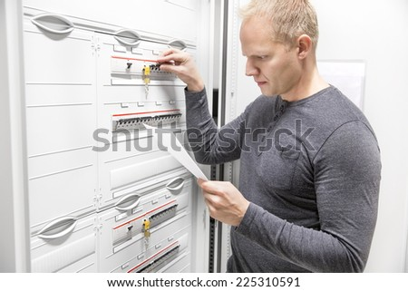 IT engineer works in large fuse cabinet - stock photo