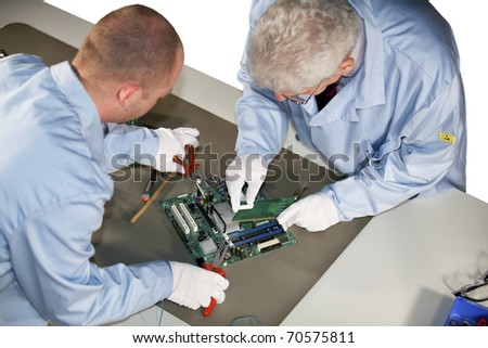 IT engineers working on a motherboard and plugging in a graphic card