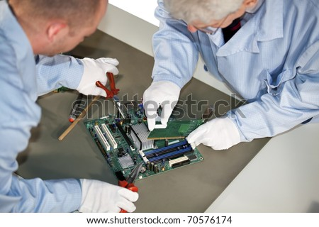 IT engineers working on a motherboard and plugging in a graphic card - stock photo