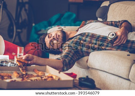 It has been a long night. Young handsome man passed out on sofa with pizza slice and beer can in his hand in messy room after party - stock photo