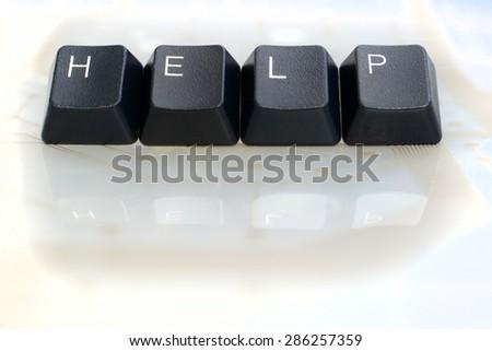 IT HELP - Four Black Keyboard Keys reading word help on White Glass Background - stock photo