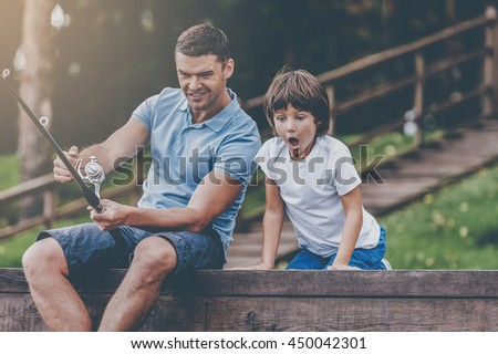 It is a big fish! Happy father and son fishing together and smiling while sitting on quayside - stock photo