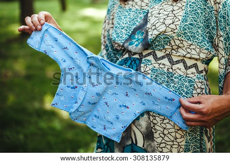 It is a boy! Cropped image of pregnant woman holding little blue shirt near her abdomen. Pregnant woman tummy  - stock photo
