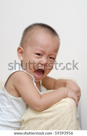 it is a cute chinese baby, he is crying and holding the sofa.