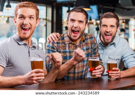 It is a goal! Three happy young men in casual wear holding glasses with beer and cheering while watching football match in bar together  - stock photo