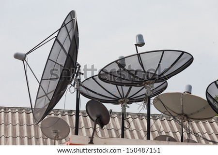 It is a lot of television satellite antennas on a house roof against the sky