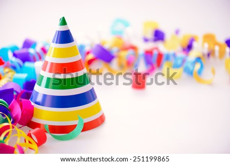 It is a special day. Image of a bright party hat surrounded by multi colored confetti and popper isolated on white background with copy space - stock photo