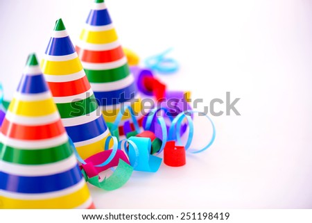 It is a special day. Image of three bright party hats with selective focus surrounded by multi colored confetti and popper isolated on white background with copy space - stock photo