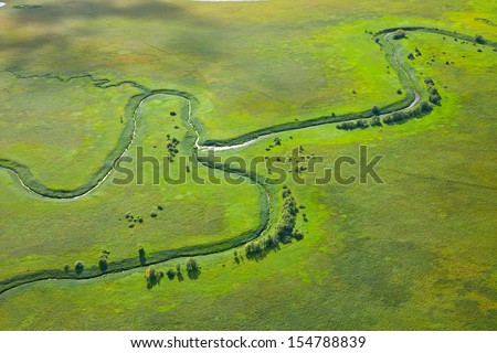 It is aerial view over the small river which is on the green floodland meadow. - stock photo
