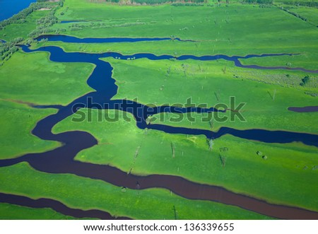 It is aerial view over the small river which is on the green meadow. - stock photo