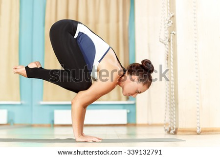 It is all about balance. Full length shot of a woman doing yoga handstand  - stock photo