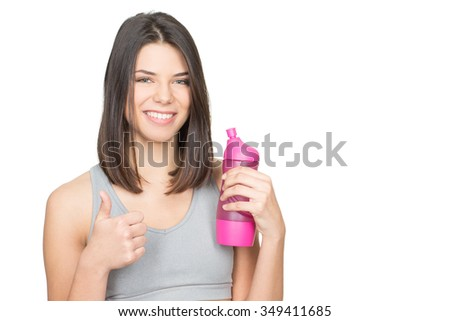 It is all about health. Beautiful young woman holding a bottle of water showing thumbs up smiling happily isolated on white copyspace on the side - stock photo