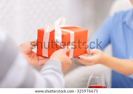 It is for you. Close up of young boy holding present and giving it to his girlfriend while having celebration - stock photo