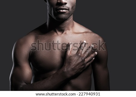 It is in my heart. Cropped image of young shirtless African man holding his hand on heart while standing against grey background - stock photo