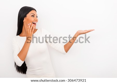 It is just amazing! Cheerful young woman holding copy space on her hand and looking at it while standing against white background