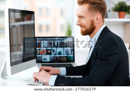 It is more than just a job. Side view of bearded businessman working on computer and smiling while sitting at his working place - stock photo
