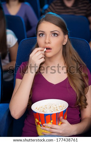 It is my favorite moment. Beautiful young woman eating popcorn and watching movie while sitting at the cinema  - stock photo