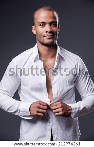 It is my favorite shirt. Handsome young black man dressing up his shirt and smiling while standing against grey background - stock photo