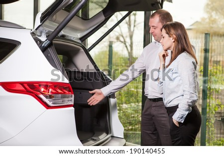 It?is so roomy inside. Handsome young car salesman showing the car trunk to the customer - stock photo