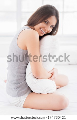 It is so soft! Side view of attractive young smiling woman sitting in bed and hugging a pillow - stock photo