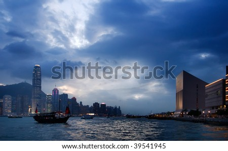 It is sunset cityscape of Victoria harbor with old Chinese style boat in Hong Kong. - stock photo