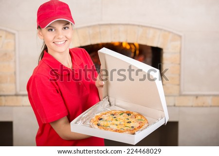 It is tasty. Delivery woman is showing the pizza. - stock photo