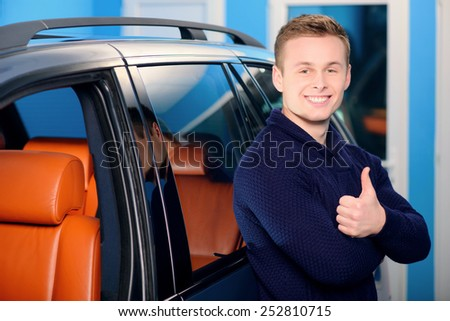 It is the best car ever. Portrait of a handsome smiling man standing by his luxury car in the garage and showing his thumb up - stock photo