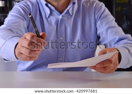 It is time to sign the document.Giving the document to sign.Business man holding a document to sign. - stock photo