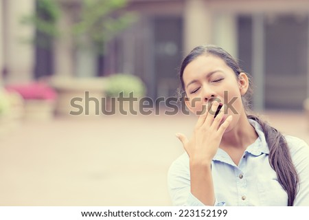 It is too early for this meeting. Portrait sleepy young business woman covering with hand wide open mouth yawning eyes closed looking bored isolated outside office background. Emotion face expression - stock photo