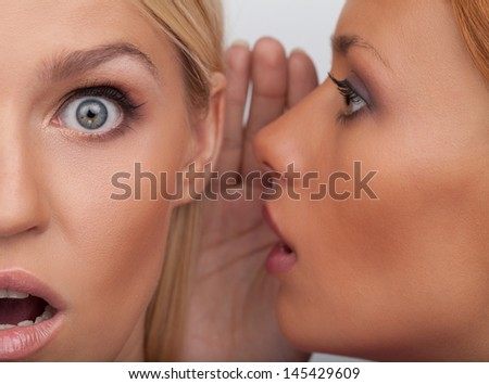 It is unbelievable! Close-up of two beautiful young women gossiping while standing isolated on white - stock photo