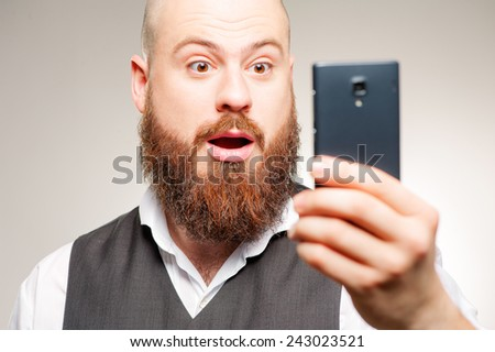 It is unbelievable! Surprised young man in shirt looking at mobile phone and keeping mouth open while standing against grey studio background - stock photo
