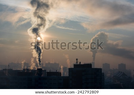 It is very cold in the morning sunrise, with smoking chimneys.  Environmental pollution. - stock photo