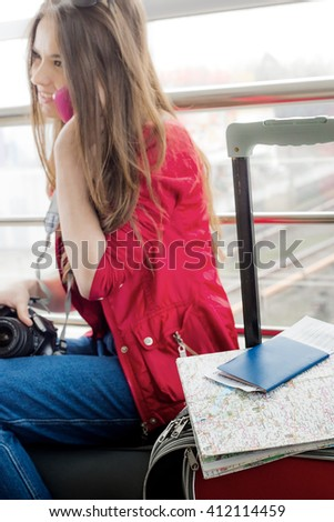 It lies on a suitcase and passport card on background girl in a red jacket, which is not in focus. - stock photo