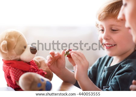 It looks so sweet. Smiling little boy holding a red strawberry while sitting with his mother at the table - stock photo
