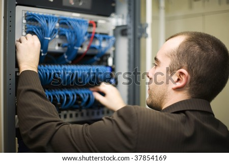IT professional. Young network administrator pluging in wires.