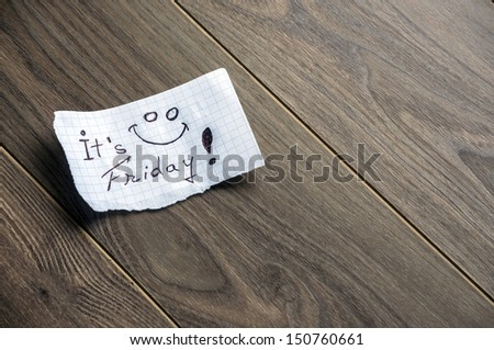 It's Friday - Hand writing text on a piece of paper on wood background with space for text - stock photo
