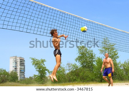 It's not a soccer - teen strikes ball into net playing beach volleyball. Shot near Dnieper river, Ukraine. - stock photo