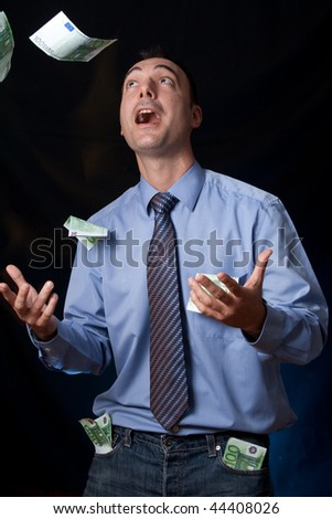 It's raining money over this rich man. His pockets are full of wads, but he's still getting even more money that falls over him. Conceptual image for easy money, rich people income, wealthy lifestyle. - stock photo