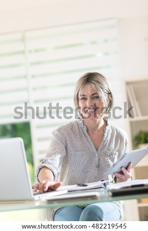it's the portrait of a middle aged woman with gray hairs who works at home with a laptop and a tablet. she is a self employed and she like what she does it, she is smiling and casual