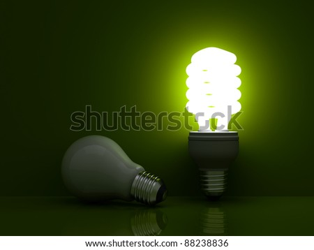 It's time for energy saving light bulb, Glowing compact fluorescent light bulb standing near unlit incandescent light bulb on green background - stock photo