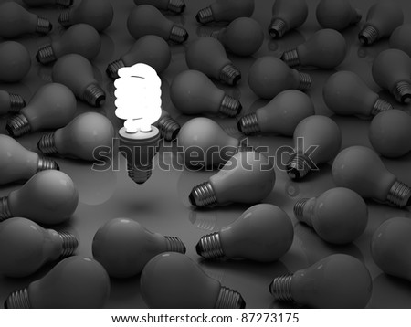 It's time for energy saving light bulb, one glowing compact fluorescent light bulb standing out from the unlit incandescent light bulbs - stock photo